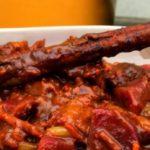 rond bord op tafelblad gevuld met stoverij recept met seitan met op achtergrond oranje stoofpot en blauw geblokte keukenhanddoek