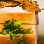 De soep van pompoen geserveerd met een chips van seitan