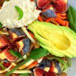 vrolijk gevuld bord met spaghetti van kleurrijke groenten afgewerkt met vijgen en avocado met vork