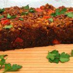 Veganistisch gehaktbrood van seitan op snijplank met tomaten en platte peterselie.