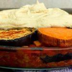 Glazen ovenschaal gevuld met vegan moussaka met seitan